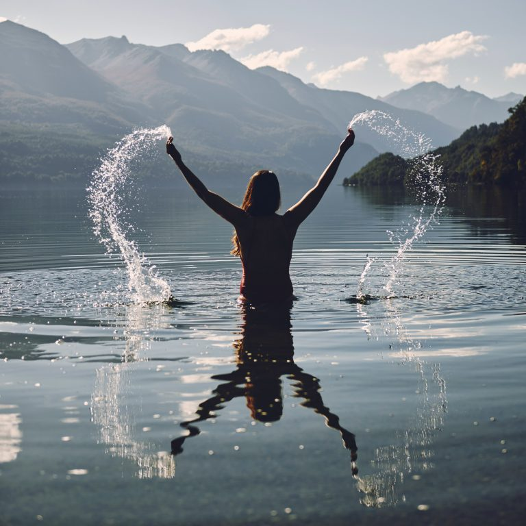 woman raising her two hands with splashing water